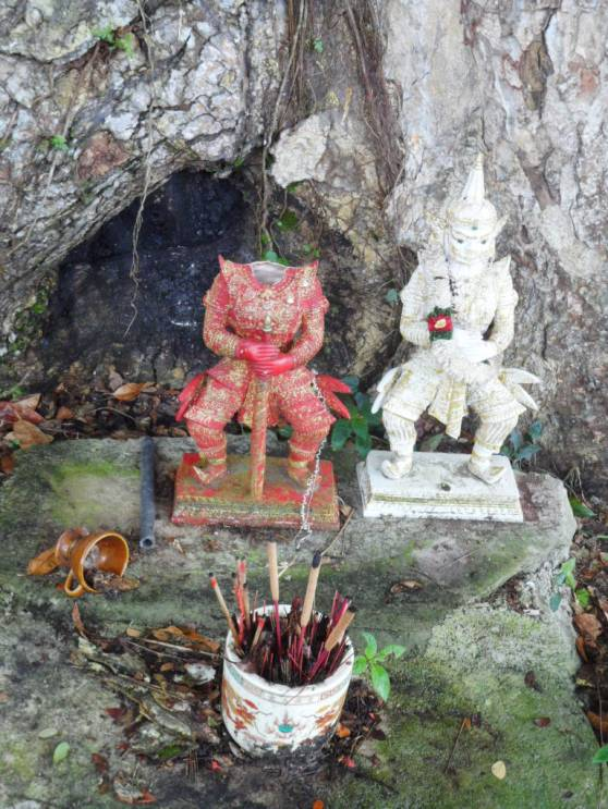 Sinister looking Thai(?) gods standing guard near the entrance under an old tree.